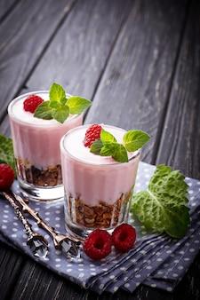 Dessert with granola, yogurt and raspberry. selective focus