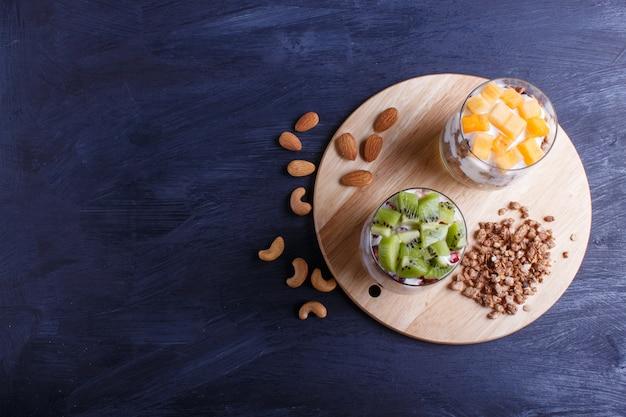 Dessert with greek yogurt, granola, almond, cashew, kiwi and persimmon on black wooden background.