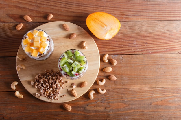 Dessert with greek yogurt, granola, almond, cashew, kiwi and persimmon on brown wooden background.