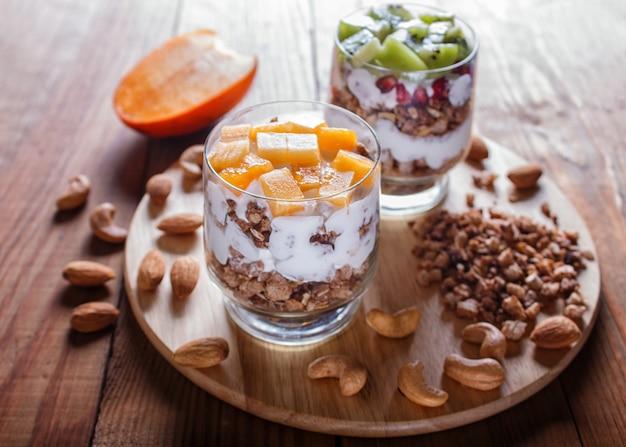 Dessert with greek yogurt, granola, almond, cashew, kiwi and persimmon on brown wooden.