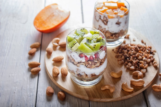 Dessert with greek yogurt, granola, almond, cashew, kiwi and persimmon on white wooden.
