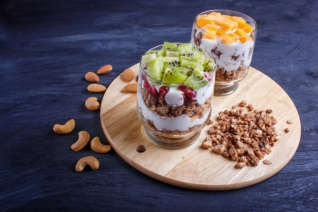 Dessert with greek yogurt, granola, almond, cashew, kiwi and persimmon on wooden surface.