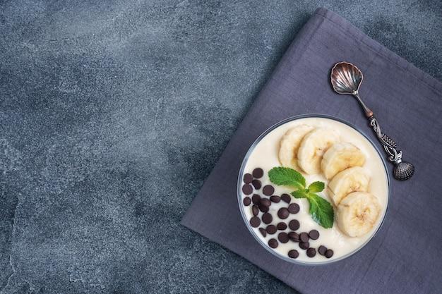 ダークブルーの背景にキッチンクロスにミルク、ヨーグルト、バナナ、チョコレートを入れたデザート