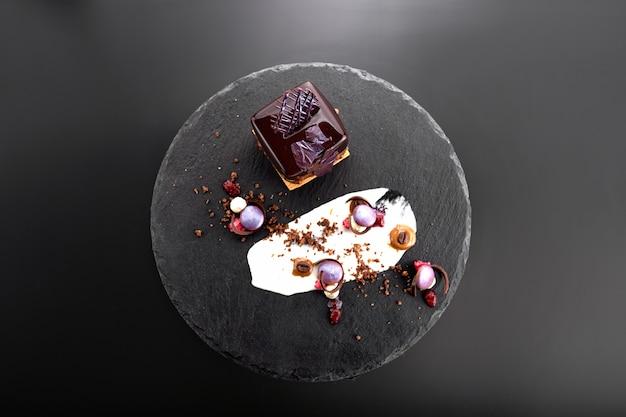 黒いスレートに立方体の形をしたチョコレート釉薬のナッツ入りデザート