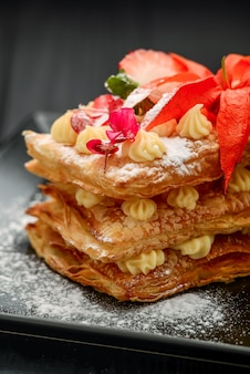 Dessert with puff pastry, cream and strawberries on a black
