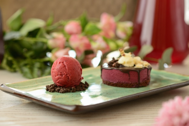 Dessert with a scoop of berry ice cream on a wooden table with flower decor