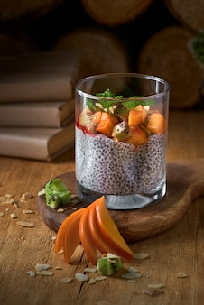 Dessert yogurt with chia seeds and fruits persimmon on a wooden dark background. healthy vegan, vegetarian breakfast table, ingredients on table