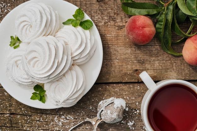 Десертный зефир (зефир) на белой тарелке, чашка чая и фрукты на столе, вид сверху, послеобеденный чай в саду. воздушные русские сладости, сервировка на винтажном столе