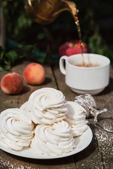 Десертный зефир (зефир) на белой тарелке, на старом деревянном столе, послеобеденный чай в саду. воздушный русский десерт крупным планом, выборочный фокус.
