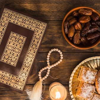 Desserts and candle near beads and quran