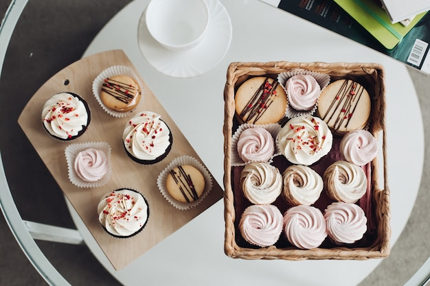 Desserts on coffee table. cupcakes with creamy topping and whipped cream in basket and wooden board with white ceramic cup and saucer..