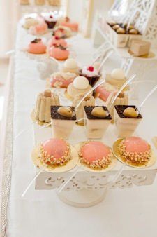 Desserts with fruits, mousse, biscuits. different types of sweet pastries, small colorful sweet cakes, macaron, and other desserts in the sweet buffet. candy bar for birthday.