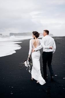 目的地のアイスランドの結婚式結婚式のカップルがvic砂浜の黒いビーチに沿って歩いています