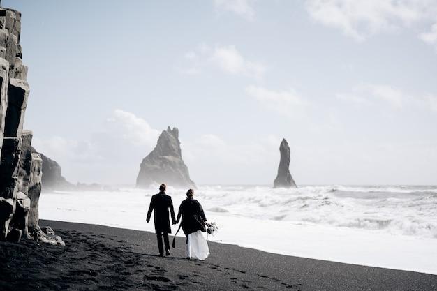 目的地のアイスランドの結婚式結婚式のカップルは近くのvikの砂浜の黒いビーチに沿って歩きます