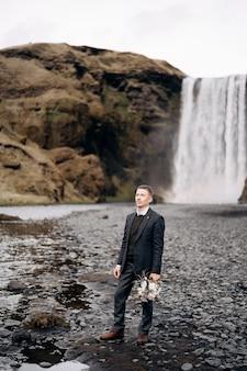 の背景に花嫁の結婚式の花束を手に持っている目的地のアイスランドの結婚式の新郎