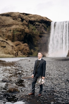 Destination iceland wedding groom with a brides wedding bouquet in hands against the backdrop of