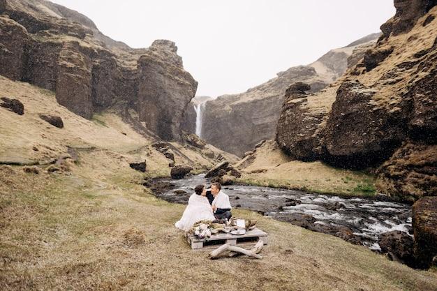 Kvernufoss滝の近くの目的地のアイスランドの結婚式結婚式のカップルが川のほとりに座っています