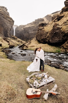 クヴェルヌフォスの滝の近くの目的地アイスランドの結婚式、結婚式のカップルが格子縞の下に立つ