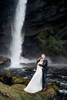 Kvernufoss滝の近くの目的地のアイスランドの結婚式結婚式のカップルが滝の近くに立っています