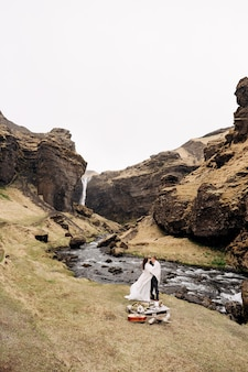 Destination iceland wedding, near kvernufoss waterfall. a wedding couple stands under a plaid near a mountain river. the groom hugs bride. they built an impromptu wedding table with decor and guitar