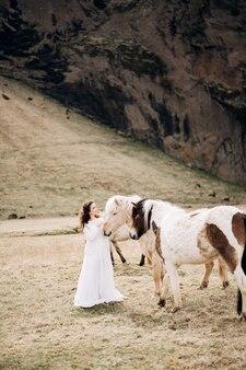 アイスランドの馬との目的地のアイスランドの結婚式のフォトセッション花嫁は2つのたてがみを撫でる