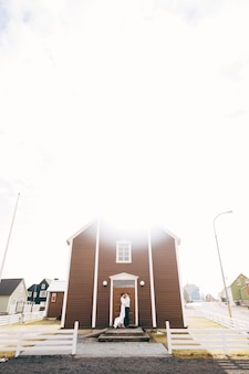 Destination iceland wedding wedding couple in front of a black church the groom hugs the bride