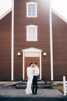 黒人教会の前で目的地のアイスランドの結婚式の結婚式のカップル新郎は花嫁を抱きしめます