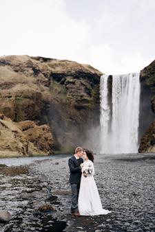 スコゥガフォスの滝の近くの目的地のアイスランドの結婚式の結婚式のカップルは、新郎新婦が抱いています