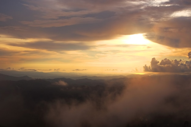 Destination and paradise of golden sunrise and sunset shining to the mist and fog in the jungle on the valley mountain. aerial view of rainy season in the tropical rainforest in thailand.