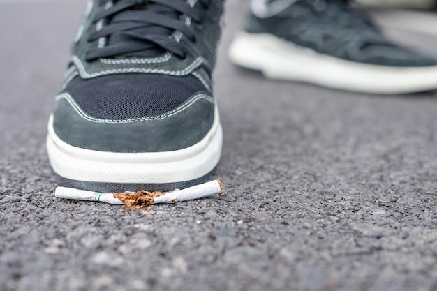 Destroy cigarette by foot. stop smoking in public area concept