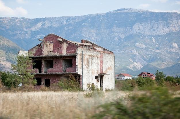 Разрушенное и заброшенное здание на поле после бомбежек.