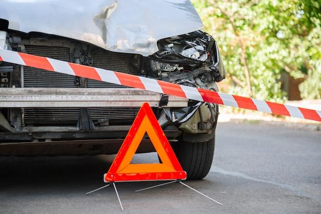 도시 도로에서 자동차 충돌 교통 사고로 자동차를 파괴했습니다. 사고로 부서진 자동차. 빨간색 비상 정지 삼각형 기호 및 빨간색 경고 경찰 테이프 전에.