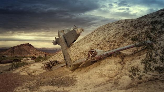 Разрушенный серый самолет на скале под серым небом
