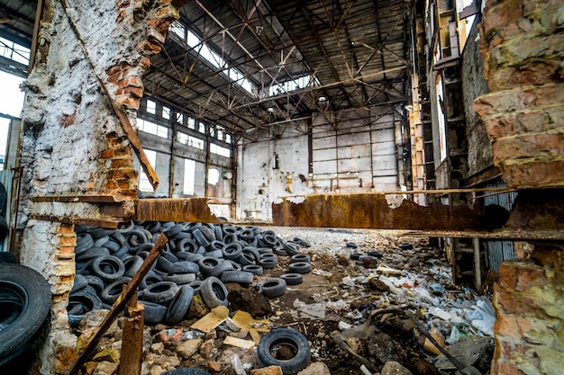 Destroyed old factory with garbage and a pile of used rubber tyres inside.