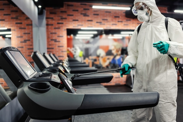 Уничтожение бактерий и вирусов на электрической беговой дорожке в современном закрытом тренажерном зале. мужчина в защитной униформе очищает зоны повышенного риска заражения. сохраняйте социальную дистанцию, коронавирус, корона, covid19