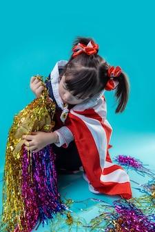 밝은 축제를 파괴합니다. 축제 장식을 조사하고 요소를 꺼내는 다운 증후군을 가진 세심한 어린 소녀