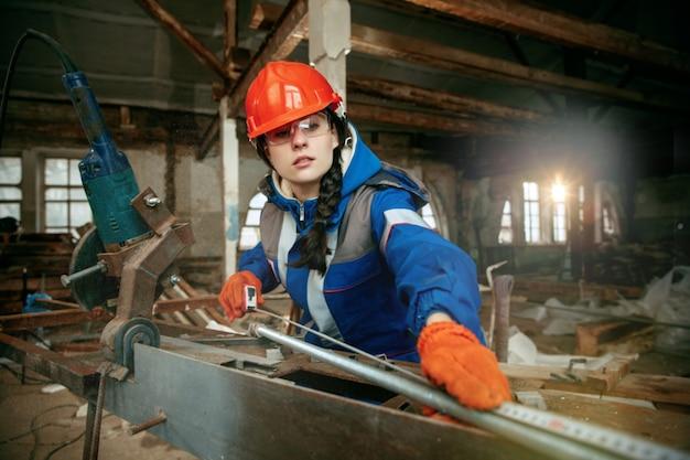 성별 고정 관념을 파괴합니다. 다른 남성 작업 도구를 사용하여 헬멧을 쓴 여자. 남녀 평등. 플랫 리모델링에서 일하는 소녀. 건물, 수리 및 개조. 남성 직업의 여성