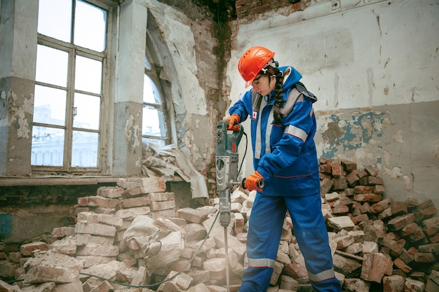 성별 고정 관념을 파괴합니다. 다른 남성 작업 도구를 사용하여 헬멧을 착용하는 여자. 남녀 평등. 플랫 리모델링에서 일하는 소녀. 건물, 수리 및 개조. 남성 직업의 여성