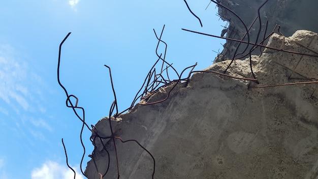 Разрушение бетонной конструкции с арматурой на фоне голубого неба. старый бетонный пол заброшенного дома.