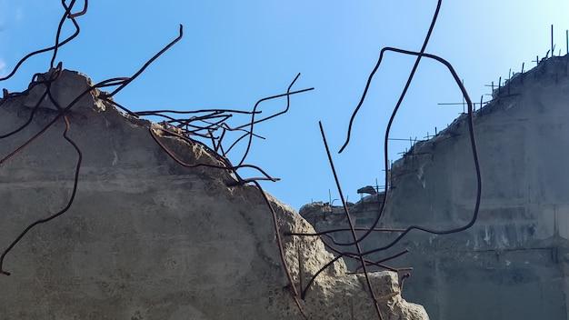 青空を背景に補強されたコンクリート構造物の破壊。廃屋の古いコンクリートの床。