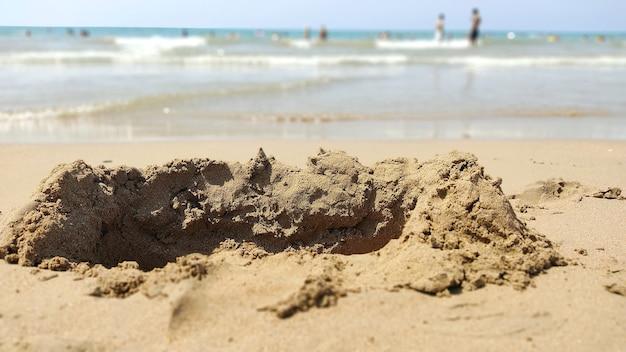 海沿いの砂の上の破壊的な波の城。休日