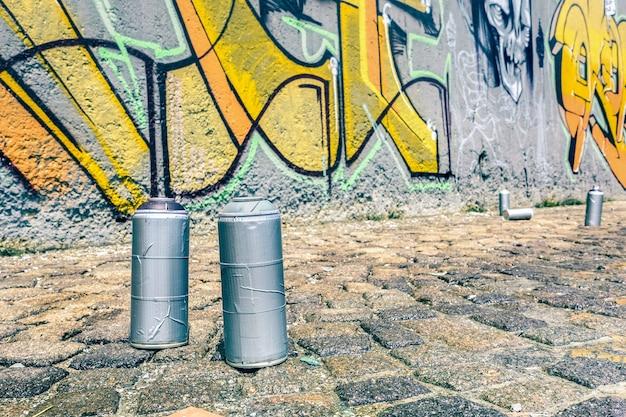 Detail of aerosol spray can at colorful graffiti on wall