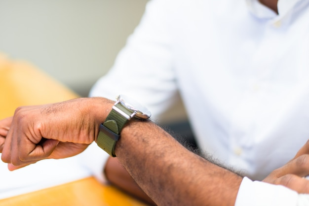 Detail of afro american businessman in the office looking dthe watch