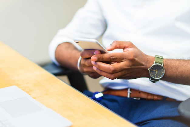 Detail of afro american businessman in the office using mobile phone