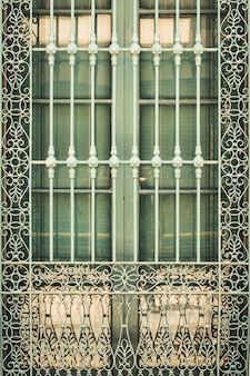 Detail on an antique wrought iron grill of a window