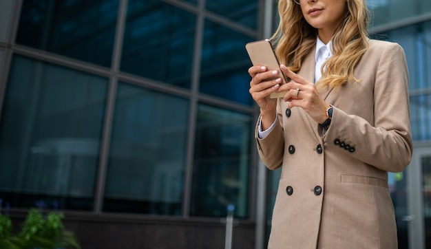 Detail of a business woman using her mobile phone