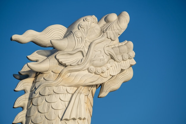 Деталь карп - статуя дракона на фоне голубого неба в городе дананг, вьетнам