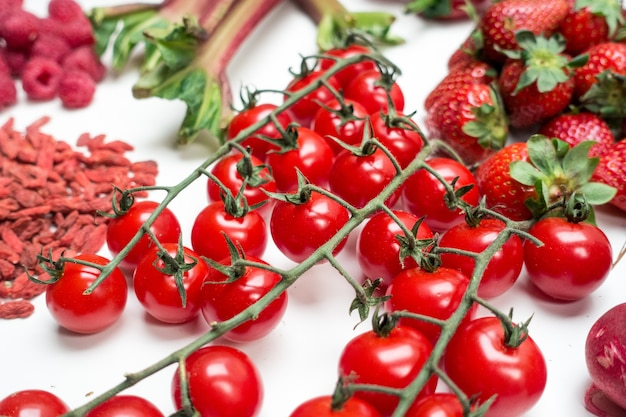 Detail of cherry tomatoes and other red fruit and vegetables on a white background