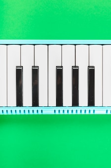 Detail of classical piano black and white keyboard on green background
