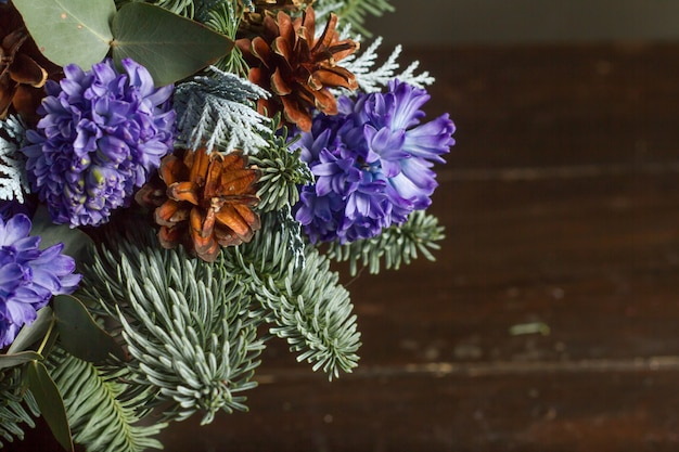 Detail close-up winter bouquet of nobil fir twigs, blue hyacinths and cones, winter gift concept